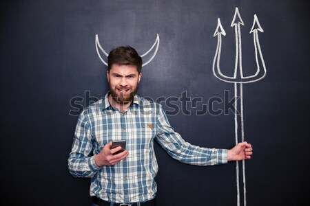 Flirty woman standing and winking over chalkboard background  Stock photo © deandrobot