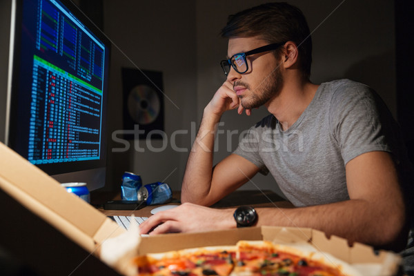 Pensive young developer in glasses coding at home Stock photo © deandrobot