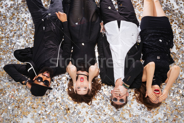 Funny friends grimacing and lying on sparkling confetti  Stock photo © deandrobot