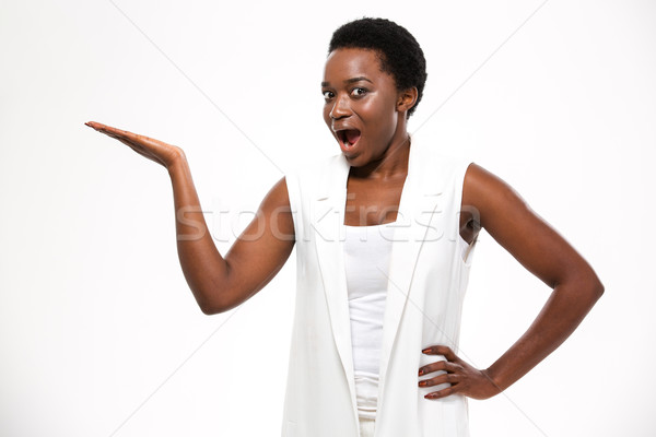 Wondered excited african woman standing and holding copyspce on palm  Stock photo © deandrobot