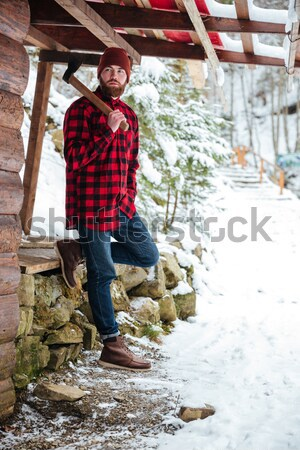 Bearded man with axe standing on wooden bridge in winter  Stock photo © deandrobot