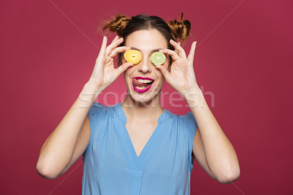 Playful woman covered eyes with jelly candies and showing tongue  Stock photo © deandrobot