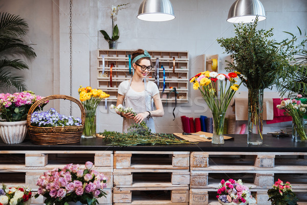 Cheerful beautiful woman florist smiling and working in flower shop Stock photo © deandrobot