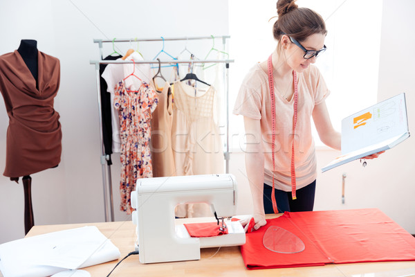 Serious woman seamstress working with red fabric in studio Stock photo © deandrobot