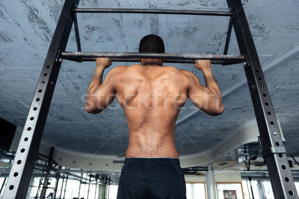 Strong athlete doing pull-up on horizontal bar Stock photo © deandrobot