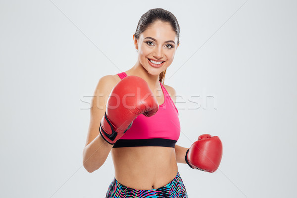 Happy woman in boxing gloves looking at camera Stock photo © deandrobot