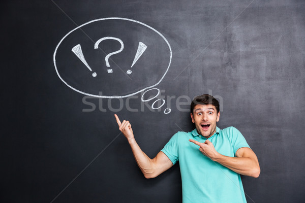 Wondered man pointing on thinking bubble over blackboard background Stock photo © deandrobot