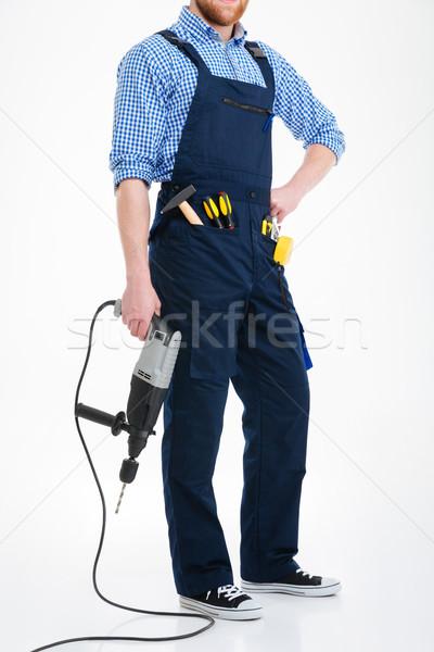 Szakállas fiatalember átfogó tart fúró férfi Stock fotó © deandrobot