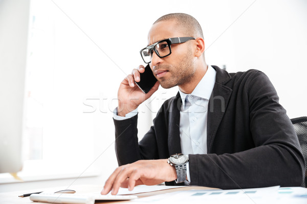 Pensive young businessman looking at computer in office Stock photo © deandrobot