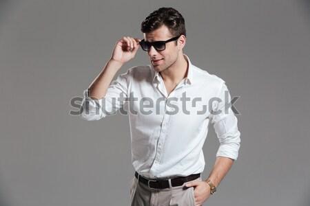 Ciddi genç beyaz gömlek kot güneş gözlüğü Stok fotoğraf © deandrobot