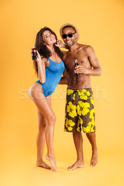 Young smiling multiracial couple holding bottles Stock photo © deandrobot