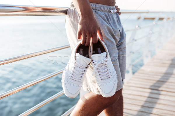 Cropped image of sportsmen hands holding sneakers at pier Stock photo © deandrobot