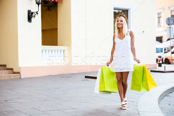 Happy young woman in hat holding shopping bags while walking Stock photo © deandrobot