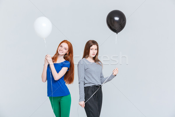 Two young women holding black and white balloons Stock photo © deandrobot