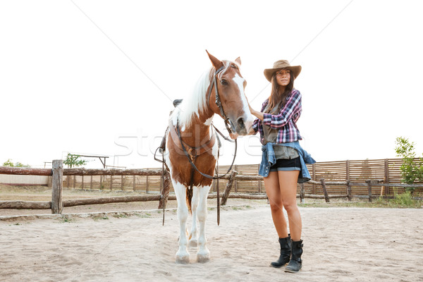 Young woman cowgirl walking with her horse in a farm Stock photo © deandrobot