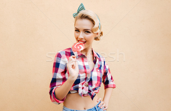 Smiling charming pin-up girl standing and eating sweet lollipop Stock photo © deandrobot