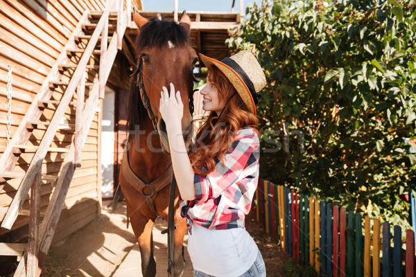Smiling woman cowgirl taking care of her horse on farm Stock photo © deandrobot