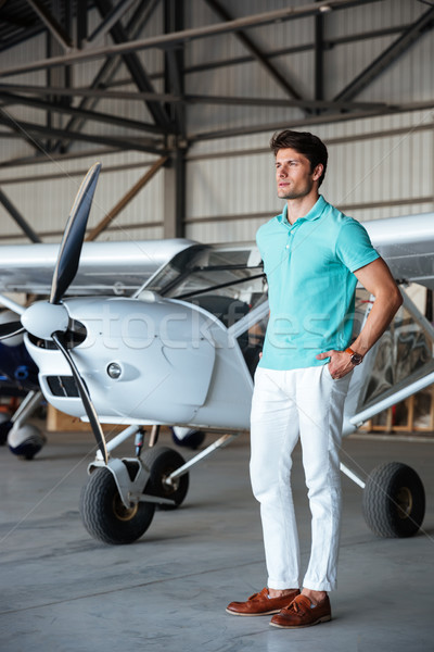 Serious attractive young man standing in front of small aircraft Stock photo © deandrobot