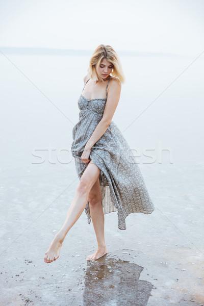 Woman walking barefoot in lake Stock photo © deandrobot