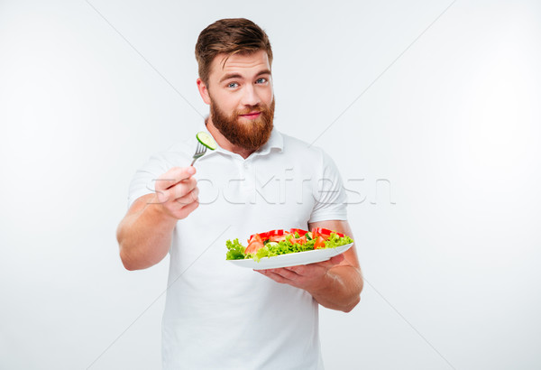 Young bearded man eating salad Stock photo © deandrobot