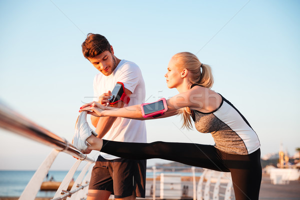 Young couple exercising and stretching muscles before sport activity Stock photo © deandrobot