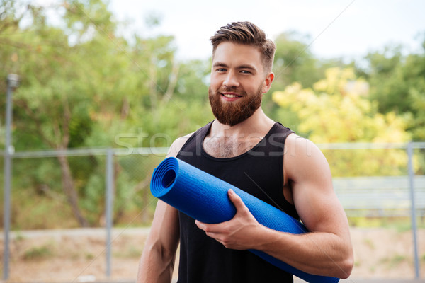Handsome bearded young sportsman holding yoga mat Stock photo © deandrobot