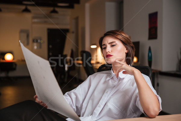 Thoughtful young woman fashion designer looking at sketches in office Stock photo © deandrobot