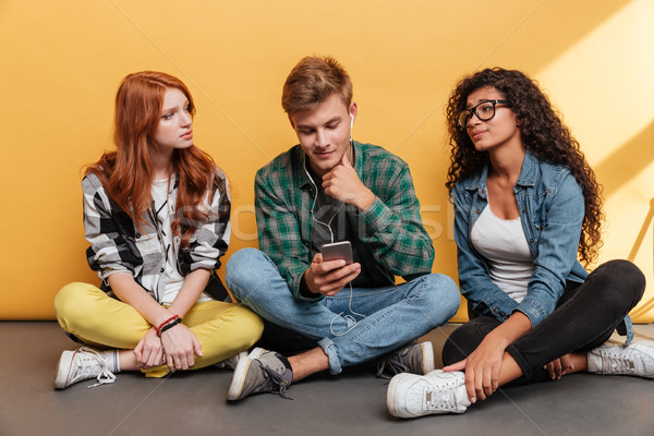 Stock photo: Love triangle of two women and man listening to music