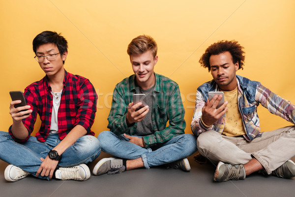 Three handsome young men friends using cell phone Stock photo © deandrobot