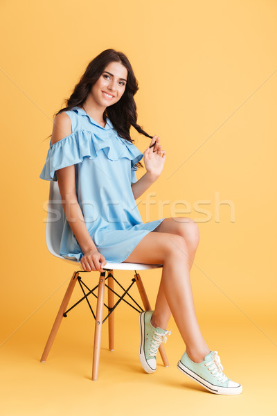 Beautiful brunette woman in blue dress posing on the chair Stock photo © deandrobot