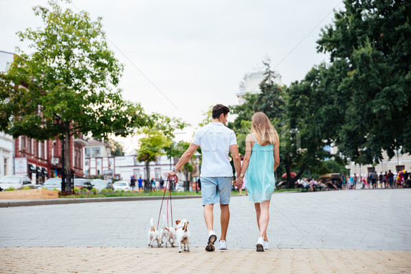 Young couple walking their dog on the city street Stock photo © deandrobot