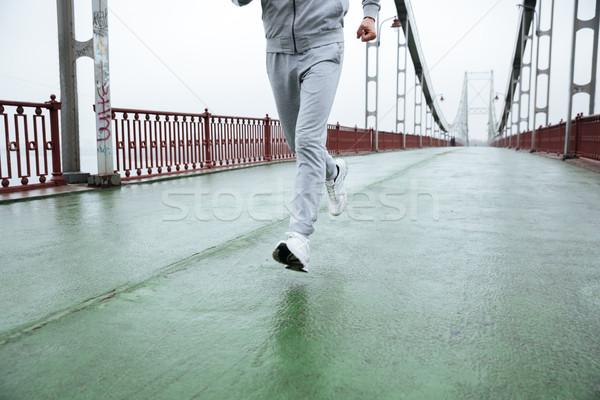 Cropped image of Man running on bridge Stock photo © deandrobot