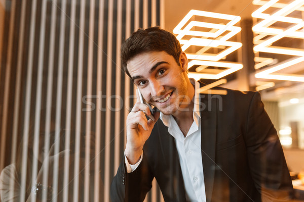 Happy businness man talking on phone behind the glass Stock photo © deandrobot