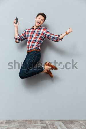 Young bearded man jumping and playing on invisible guitar Stock photo © deandrobot