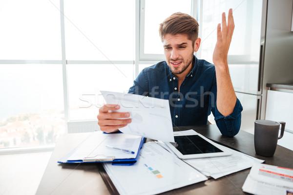 Szomorú férfi gesztikulál kéz néz iratok Stock fotó © deandrobot