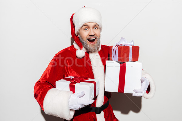 Cheerful man santa claus standing and holding present boxes Stock photo © deandrobot