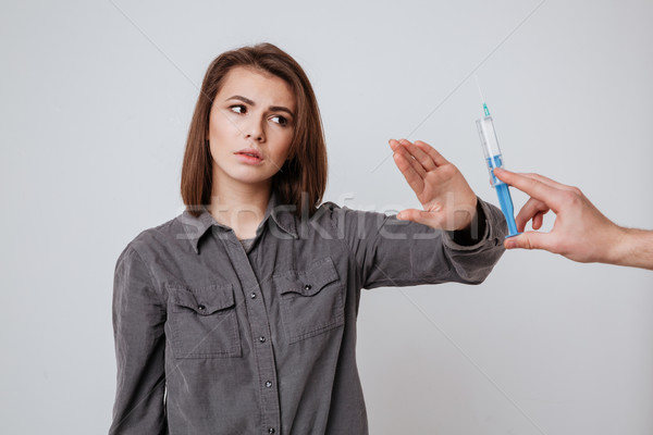 Woman make stop gesture to syringe. Stock photo © deandrobot