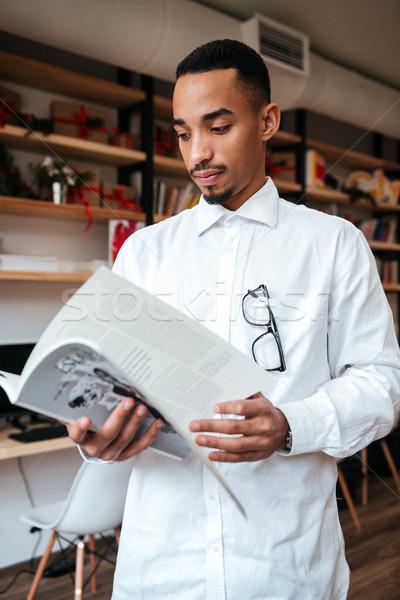 Bello african imprenditore guardare magazine immagine Foto d'archivio © deandrobot