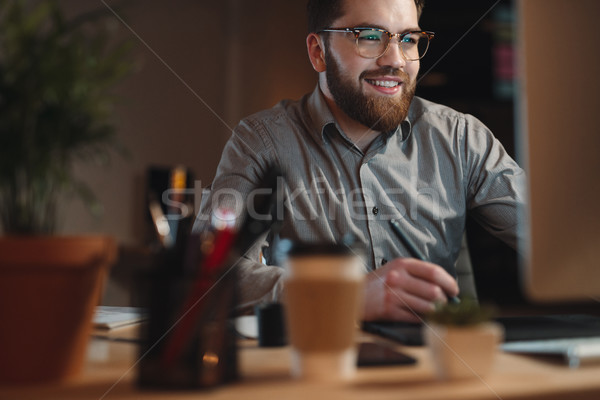 Smiling bearded web designer working late at night Stock photo © deandrobot