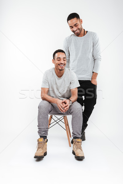 Cheerful african men posing over white background Stock photo © deandrobot