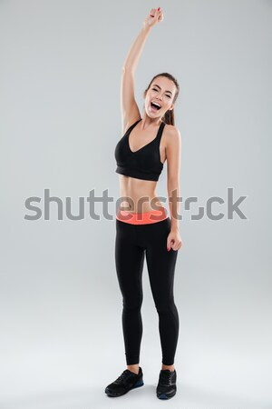 Attractive young woman athlete with armband and earphones standing Stock photo © deandrobot