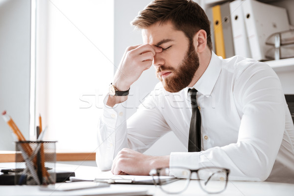 Annoiato giovani imprenditore seduta ufficio foto Foto d'archivio © deandrobot