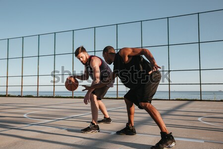 Two basketball players having game at the playground Stock photo © deandrobot