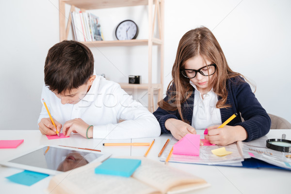 Little boy and girl writing on sticky notes at table Stock photo © deandrobot