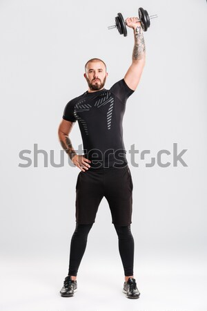 Full length portrait of muscular man with barbell Stock photo © deandrobot