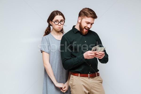 Upset Female nerd with bearded man which recounts money Stock photo © deandrobot