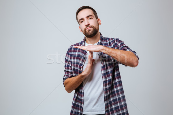 Serious Bearded man in shirt showing time out sign Stock photo © deandrobot