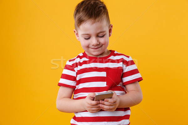 Clever young boy typing message on mobile phone Stock photo © deandrobot
