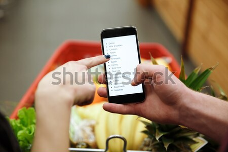 Young man in supermarket looking at list of purchases Stock photo © deandrobot