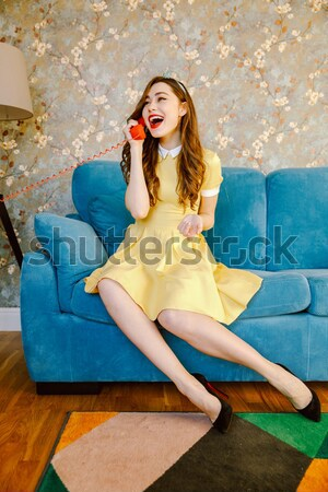 Pretty young pin-up lady choose between stationary and mobile phone. Stock photo © deandrobot